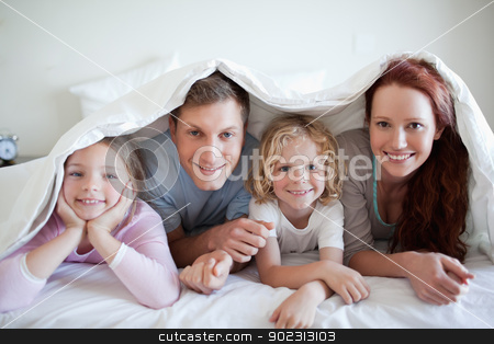 Happy family under bed cover stock photo, Happy smiling family under bed cover by Wavebreak Media