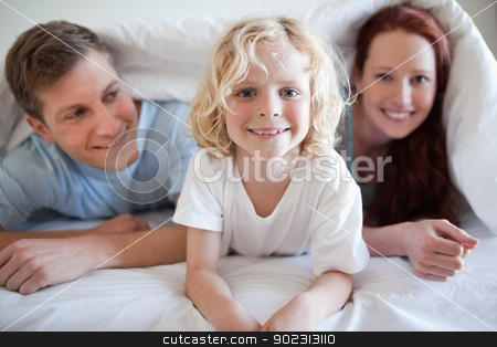 Smiling boy under the cover with his parents stock photo, Happy smiling boy under the cover with his parents by Wavebreak Media