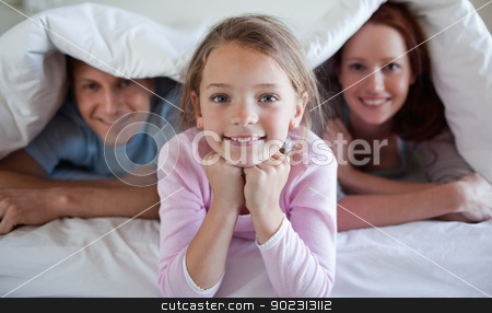 Girl under bed cover with parents stock photo, Girl under bed cover with her parents by Wavebreak Media