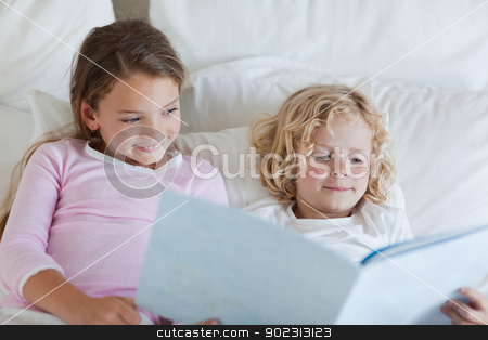 Brother and sister reading bed time story stock photo, Brother and sister reading bed time story together by Wavebreak Media