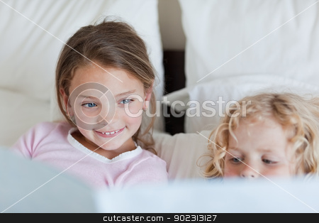 Girl reading a fairy tale for her brother stock photo, Girl reading a fairy tale for her little brother by Wavebreak Media