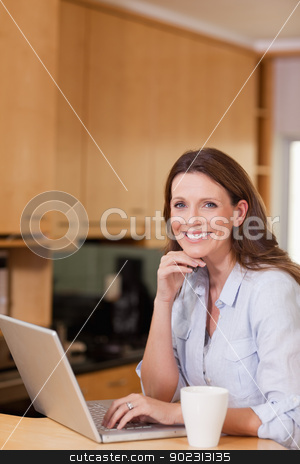 Smiling woman with laptop in the kitchen stock photo, Happy smiling woman with laptop in the kitchen by Wavebreak Media