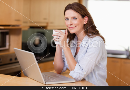 Woman drinking coffee while on laptop stock photo, Woman drinking coffee while on her laptop by Wavebreak Media