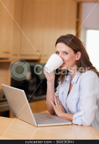 Woman taking a sip of coffee next to laptop stock photo, Woman taking a sip of coffee next to her laptop by Wavebreak Media