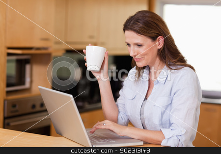 Woman drinking tea while on laptop stock photo, Woman drinking tea while on her laptop by Wavebreak Media