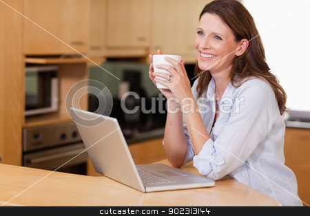 Woman with cup and notebook in the kitchen stock photo, Smiling woman with cup and notebook in the kitchen by Wavebreak Media