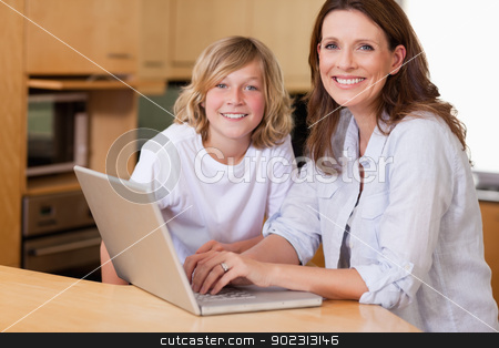 Mother and son with laptop stock photo, Mother and son with laptop in the kitchen by Wavebreak Media