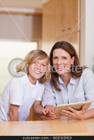 Woman and her son using tablet in the kitchen stock photo, Woman and her son using tablet in the kitchen together by Wavebreak Media