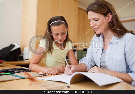 Mother helping daughter with her homework stock photo, Mother helping her daughter with her homework by Wavebreak Media