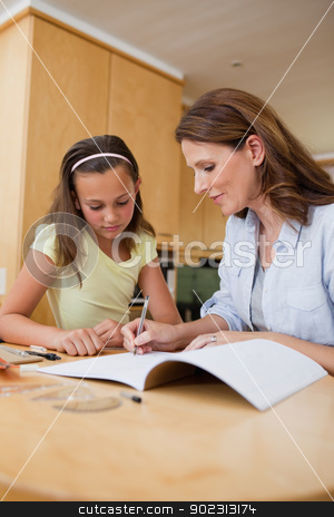 Woman helping daughter with homework stock photo, Woman helping her daughter with homework by Wavebreak Media