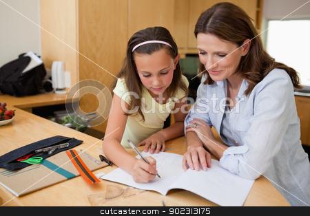 Girl doing homework with her mother stock photo, Girl doing homework together with her mother by Wavebreak Media