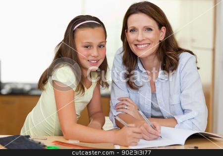Woman helping her daughter with homework stock photo, Woman helping her daughter with her homework by Wavebreak Media