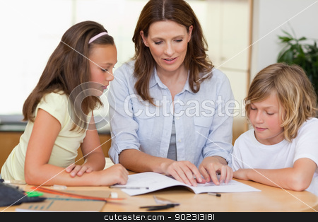 Woman helping children with homework stock photo, Woman helping her children with homework by Wavebreak Media