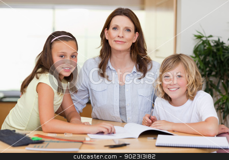 Woman helping her children with homework stock photo, Woman helping her children with their homework by Wavebreak Media