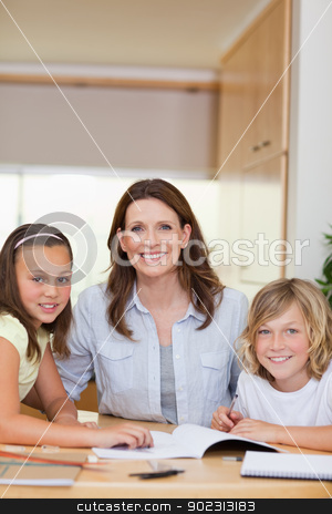 Mother helping children with homework stock photo, Mother helping her children with homework by Wavebreak Media