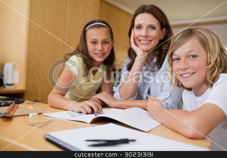 Mother doing homework with children stock photo, Mother doing homework with her children by Wavebreak Media