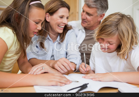Siblings getting help with homework from parents stock photo, Siblings getting help with homework from their parents by Wavebreak Media