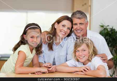 Family together behind table stock photo, Smiling family together behind table by Wavebreak Media