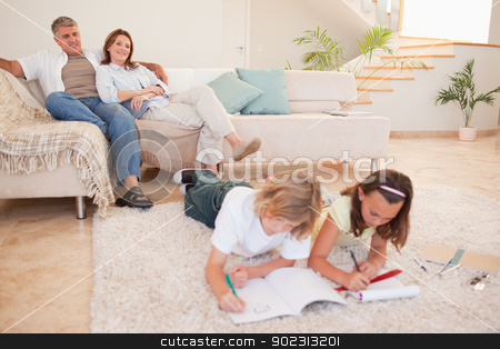 Children doing homework with parents behind them stock photo, Children doing homework with their parents behind them by Wavebreak Media
