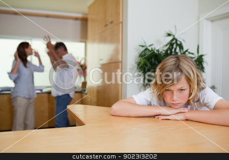 Boy is sad about fighting parents stock photo, Boy is sad about fighting parents behind him by Wavebreak Media