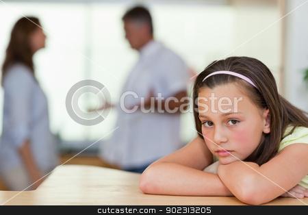 Sad girl with fighting parents behind her stock photo, Sad girl with her fighting parents behind her by Wavebreak Media