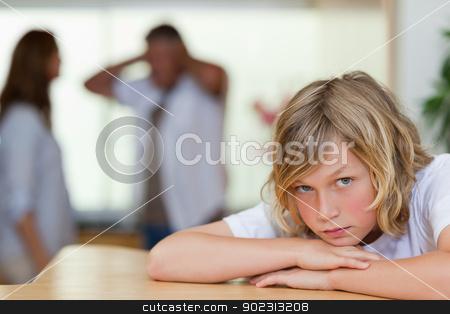 Sad looking boy with arguing parents behind him stock photo, Sad looking boy with his arguing parents behind him by Wavebreak Media