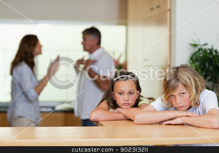 Sad looking siblings with arguing parents behind them stock photo, Sad looking siblings with their arguing parents behind them by Wavebreak Media