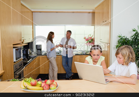Children with laptop in the kitchen and parents behind them stock photo, Children with their laptop in the kitchen and parents behind them by Wavebreak Media