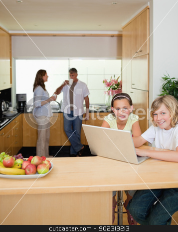Siblings with laptop in the kitchen with parents behind them stock photo, Siblings with their laptop in the kitchen with parents behind them by Wavebreak Media