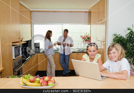 Children with notebook in the kitchen and parents behind them stock photo, Children with their notebook in the kitchen and parents behind them by Wavebreak Media