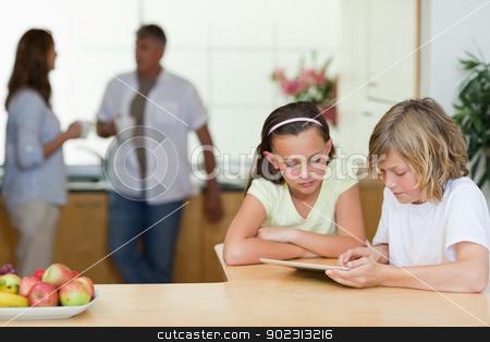 Children using tablet in the kitchen with parents behind them stock photo, Children using tablet in the kitchen with their parents behind them by Wavebreak Media