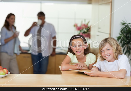 Siblings using tablet in the kitchen with parents behind them stock photo, Siblings using tablet in the kitchen with their parents behind them by Wavebreak Media