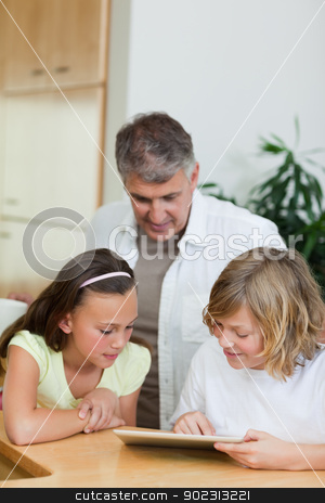 Boy with tablet showing things to sister and father stock photo, Boy with tablet showing things to his sister and father by Wavebreak Media