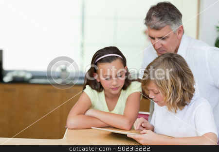 Father together with children and tablet in the kitchen stock photo, Father together with his children and tablet in the kitchen by Wavebreak Media