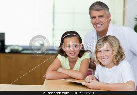 Smiling man with children and tablet in the kitchen stock photo, Smiling man with his children and tablet in the kitchen by Wavebreak Media