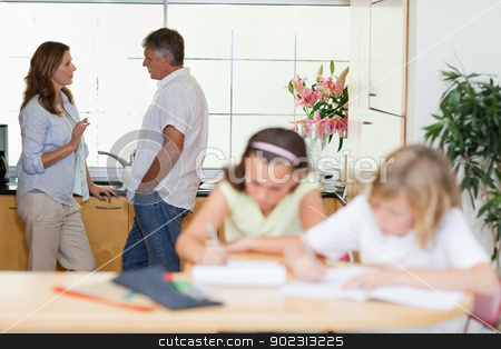 Parents talking with children doing homework in front of them stock photo, Parents talking with their children doing homework in front of them by Wavebreak Media