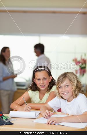Children doing homework with their parents behind them stock photo, Children doing their homework with their parents behind them by Wavebreak Media