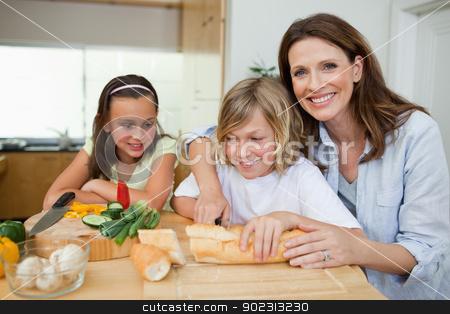 Mother making sandwiches with her children stock photo, Mother making sandwiches together with her children by Wavebreak Media