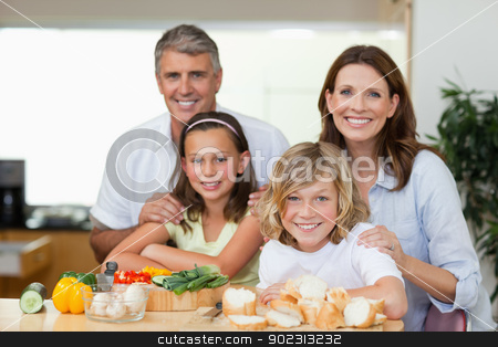 Smiling family making sandwiches stock photo, Smiling family making sandwiches together by Wavebreak Media