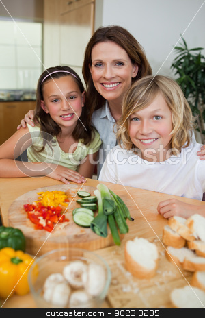 Smiling mother making sandwiches with her children stock photo, Smiling mother making sandwiches together with her children by Wavebreak Media