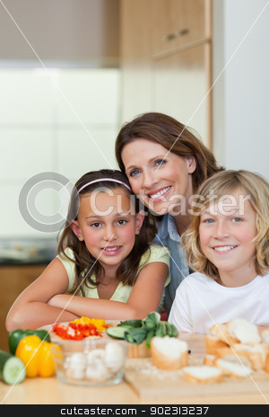 Smiling siblings and mother making sandwiches stock photo, Smiling siblings and mother making sandwiches together by Wavebreak Media
