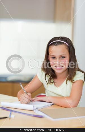 Smiling girl doing homework stock photo, Smiling girl doing her homework by Wavebreak Media