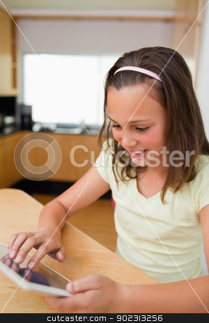 Girl using tablet at the kitchen table stock photo, Little girl using tablet at the kitchen table by Wavebreak Media