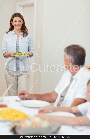 Mother bringing salad to the dinner table stock photo, Smiling mother bringing salad to dinner table by Wavebreak Media