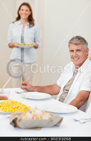 Man waiting for his wife to bring salad to the table stock photo, Man waiting for his wife to bring salad to the dinner table by Wavebreak Media