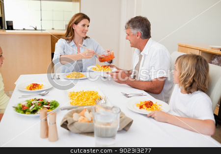 Woman serving dinner to hungry family stock photo, Woman serving dinner to her hungry family by Wavebreak Media