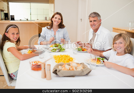 Smiling family having dinner stock photo, Smiling family having dinner together by Wavebreak Media