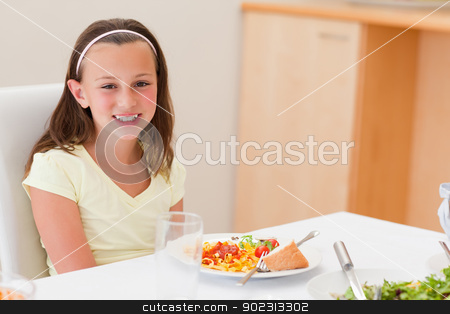 Smiling girl with dinner at the table stock photo, Smiling girl with her dinner at the table by Wavebreak Media