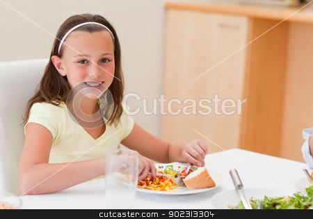 Smiling girl having dinner at dinner table stock photo, Smiling girl having dinner at the dinner table by Wavebreak Media