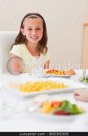 Smiling girl sitting at dinner table stock photo, Smiling girl sitting at the dinner table by Wavebreak Media